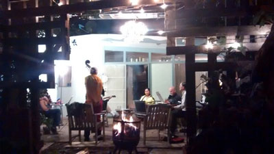 Several musicians, including a stand-up bass, on an outdoor patio at night.